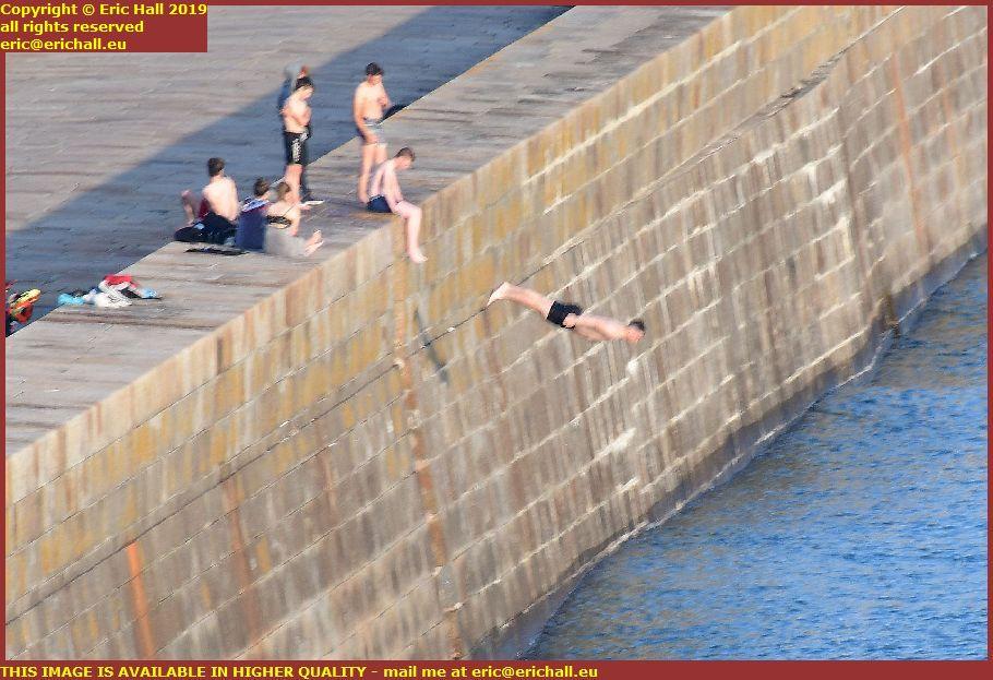 youths diving off sea wall port de granville harbour manche normandy france